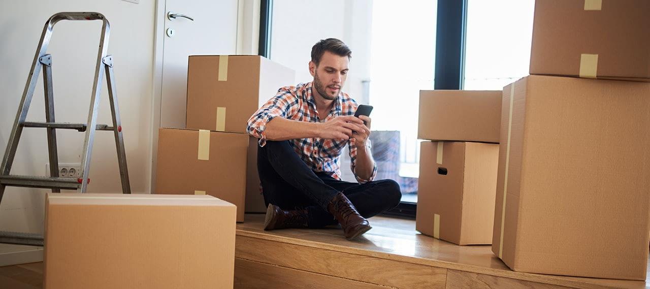 Mann sitzt mit Handy zwischen Umzugskisten